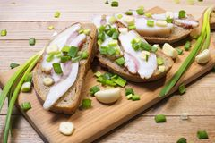 Sandwich with bacon and green onion with garlic on a wooden cutting board. Sandwich with bacon on slices of rye bread and green onions with garlic on a wooden Royalty Free Stock Image