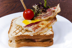 Sandwich with bacon. Scrambled eggs and vegetables close-up royalty free stock images