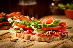 Sandwich with bacon and vegetables on vintage wooden board Stock Image