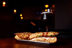 Sandwich in a bar on a wooden table. A tulip glass of beer on the background. stock photos