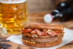 Sandwich with beef, fried onion, cheese and bacon with granular mustard. Beer and snack on the table. Rustic style.  Selective focus Stock Photos