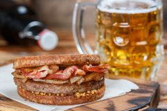 Sandwich with beef, fried onion, cheese and bacon with granular mustard. Beer and snack on the table. Rustic style.  Selective focus Royalty Free Stock Images