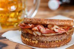 Sandwich with beef, fried onion, cheese and bacon with granular mustard. Beer and snack on the table. Rustic style.  Selective focus Royalty Free Stock Image