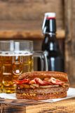 Sandwich with beef, fried onion, cheese and bacon with granular mustard. Beer and snack on the table. Rustic style.  Selective focus Stock Image