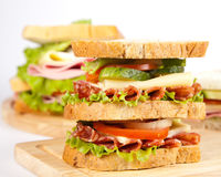 Sandwich. Big sandwich with fresh vegetables on wooden board stock photo
