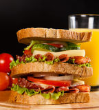 Sandwich. Big sandwich with fresh vegetables on wooden board on black background stock photo