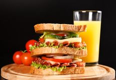 Sandwich. Big sandwich with fresh vegetables on wooden board on black background stock photos