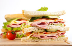 Sandwich. Big sandwich with fresh vegetables on wooden board on white background stock photography