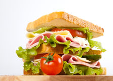 Sandwich. Big sandwich with fresh vegetables on wooden board on white background royalty free stock image