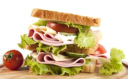 Sandwich. Big sandwich with fresh vegetables on wooden board on white background royalty free stock photos