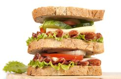 Sandwich. Big sandwich with fresh vegetables on wooden board on white background royalty free stock photo