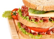 Sandwich. Big sandwich with fresh vegetables on wooden board on white background royalty free stock images