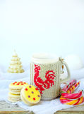 Sandwich biscuits with yellow icing sprinkled with sugar stars and cup of tea on light wooden background. Stock Images