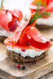 Sandwich of black bread, cheese with herbs and red salmon. Stock Images