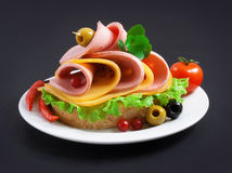 Sandwich with boiled sausage, greens and cheese on a white plate Royalty Free Stock Image
