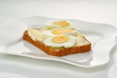 Sandwich with bread, butter, egg and cheese on a white plate and white background, close-up stock photo