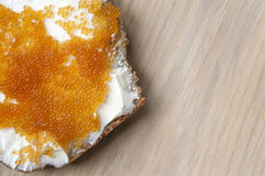 Sandwich of bread and pike caviar on light wooden surface. Royalty Free Stock Images