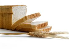 Sandwich bread sliced ​​into slices and a ear of wheat. Sliced ​​bread for sandwiches cut into slices and a ear of wheat placed on a royalty free stock photos