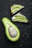 Sandwich for breakfast from fresh avocado, black diet bread, cheese and sesame, upright stock photos