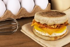 Sandwich breakfast with ingredients in background. English muffin, egg, cheese and bacon stock photos