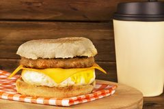 Sandwich breakfast with wooden plank in background. English muffin, egg, cheese, and sausage stock photography