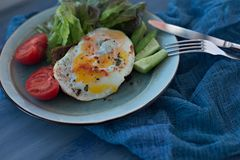Sandwich bruschetta with fried egg on a plate. With lettuce, tomatoes and cucumber. Close up stock image