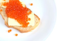 Sandwich with butter and red caviar on white bread lies on a round plate, isolated over white Royalty Free Stock Image