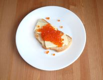 Sandwiches with butter and red caviar on white bread lies on white round plate on wooden background. Sandwich with butter and red salmon caviar on white bread Royalty Free Stock Photos