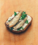 Sandwich of canned sprats on rye bread with mayonnaise and parsley, and dill on a wooden cutting board Royalty Free Stock Photography