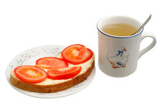 Sandwich and cap of tea. Sandwich with butter and tomatoes isolated on white background Stock Images