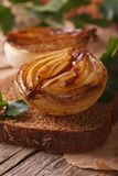 Sandwich with caramelized onions macro on an old table, vertical Stock Photos