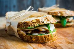 Sandwich with cereal bread, chicken, pesto and cheese on the rustic wooden background. Selective focus. Shallow depth of field Stock Photos