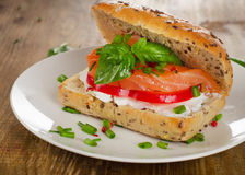 Sandwich with cereals bread and salmon on a old wooden table. Royalty Free Stock Images