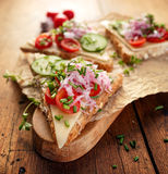 Sandwich with cheese, cherry tomatoes, cucumber, radish and fresh chives on wooden board Royalty Free Stock Image