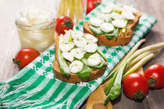 Sandwich with cheese. Sandwich with mozzarella,ramson and tomatoes in studio Royalty Free Stock Photos