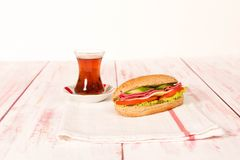 Sandwich with cheese, tomato, salami, cucumber and lettuce on wo. Fresh and tasty sandwich with tea on cloth napkin Royalty Free Stock Images