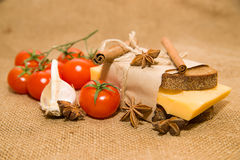 Sandwich with cheese wrapped in paper,cinnamon stick, cherry tom Royalty Free Stock Photos