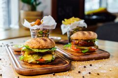 Mouth-watering delicious homemade burger used to chop beef on the wooden table. royalty free stock photo
