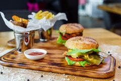 Mouth-watering delicious homemade burger used to chop beef on the wooden table. stock photography