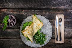 Sandwich with chicken and vegetables on a ceramic plate. Served with cutlery and fresh lemonade. Top view royalty free stock image