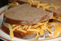 Sandwich closeup. Closeup of rye bread slices with grated cheese and jam on a plate Stock Photos