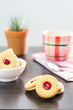 Sandwich cookies with cream and strawberry flavoured jam on wood Stock Photography