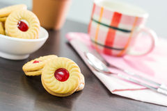 Sandwich cookies with cream and strawberry flavoured jam on wood Stock Images