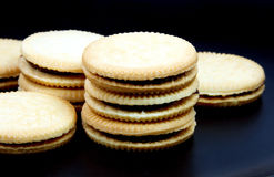Sandwich cookies filled with chocolate cream on black background. Royalty Free Stock Photo