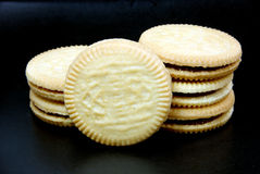 Sandwich cookies filled with chocolate cream on black background. Royalty Free Stock Photography