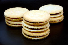 Sandwich cookies filled with chocolate cream on black background. Royalty Free Stock Images