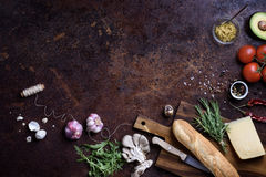 Sandwich cooking ingredients. French baguette with cheese and vegetables over rustic counter top. View above, copy space. Bread royalty free stock photos