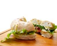 Sandwich coupé en tranches à bagel avec des légumes sur une planche à découper en bois photo libre de droits