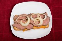 Sandwich coupé en tranches chaud à boeuf avec des anneaux d'oignon sur le Tableau rouge Photo libre de droits