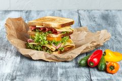 Sandwich,kraft paper sandwich. Sandwich on craft paper, on a wooden background, from different angles, with vegetables stock image